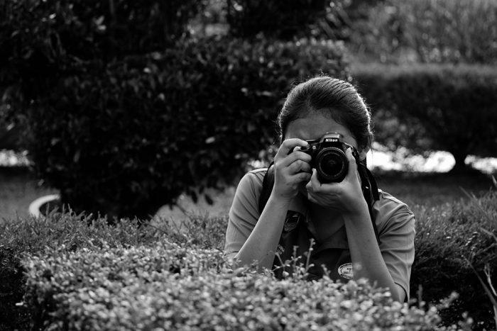 カメラのファインダーをのぞく女性の写真